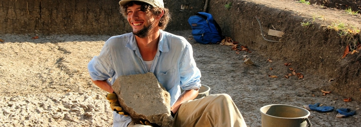 archaeology student holding an ancient artefact