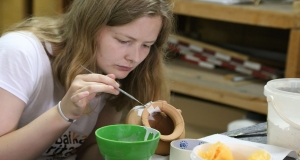 student uses conservation technique on roman pottery