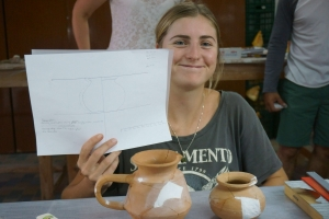 student showing drawing of pottery