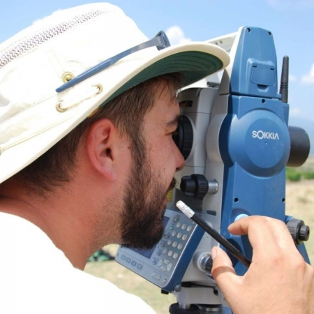 archaeologist operating a total station