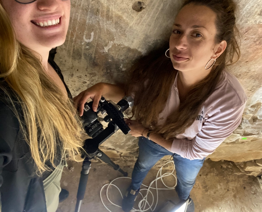 two young woman holding a camera